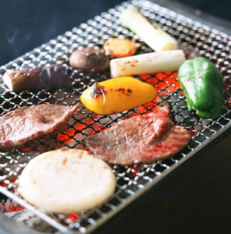 Meat, onion, potato and green pepper are on barbecue grill mesh. Under mesh, it is charcoal oven and the charcoal is burning.